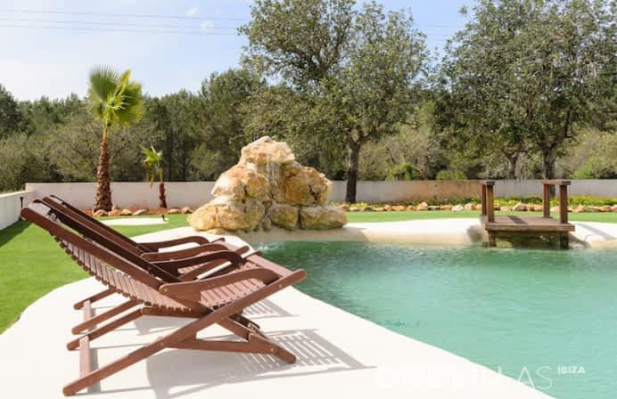 Zwembad met ligstoelen en bomen