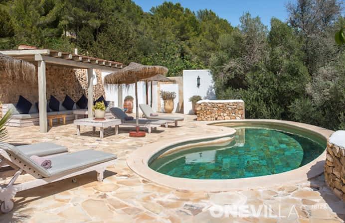 Klein zwembad met ligbedden en loungebanken