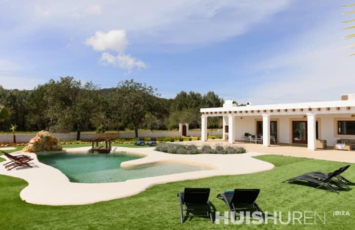 Grasveld met ligbedden en zwembad